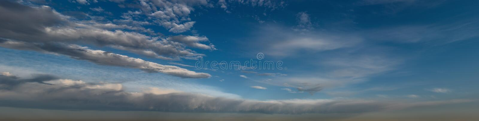 Silver clouds panorama. Silver clouds mass on the horizon below the blue sky in a sweeping panoramic view stock image