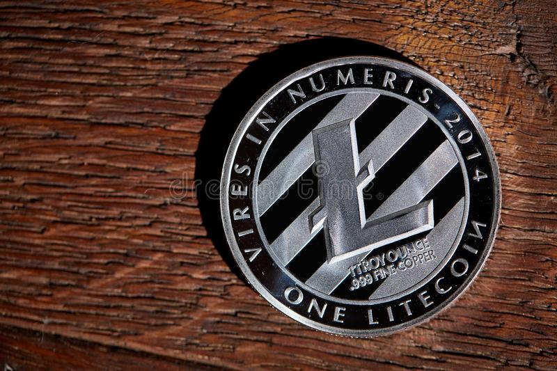 Silver coin of digital crypto currency with the symbol of Litecoin on a wooden background, close-up, macro. Silver coin of digital crypto currency with the stock photo