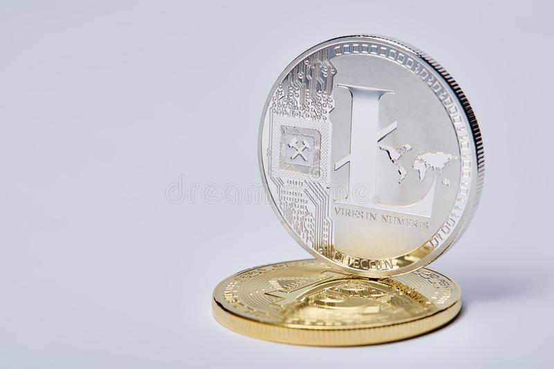 Silver coin of digital crypto currency with the symbol of Litecoin on a white background, close-up, macro. Silver coin of digital crypto currency with the symbol royalty free stock image