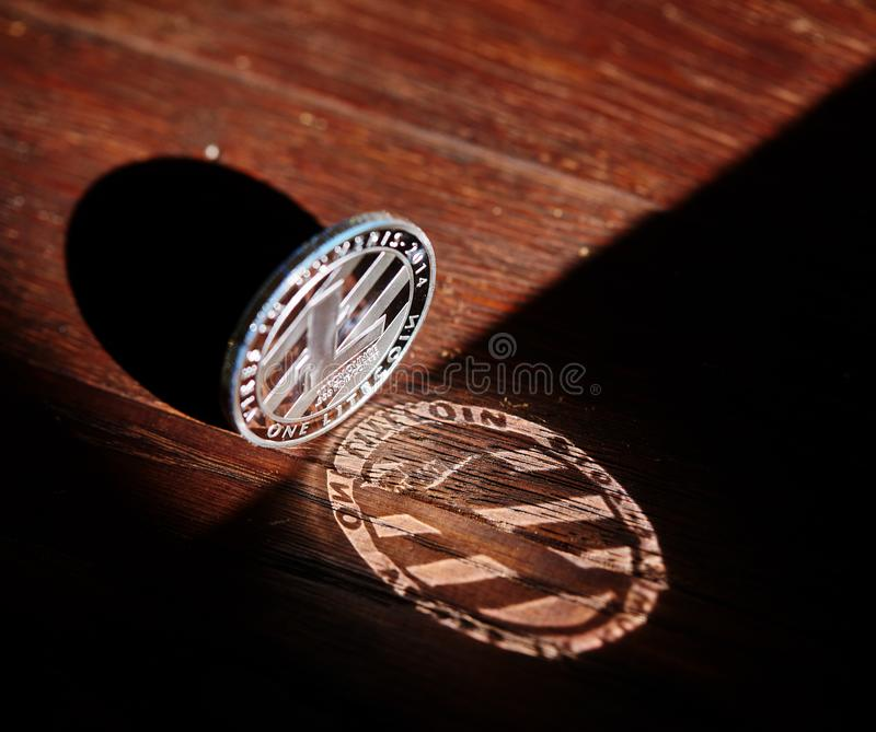 Silver coin of digital crypto currency with the symbol of Litecoin on a wooden background, close-up, macro. Silver coin of digital crypto currency with the royalty free stock photos