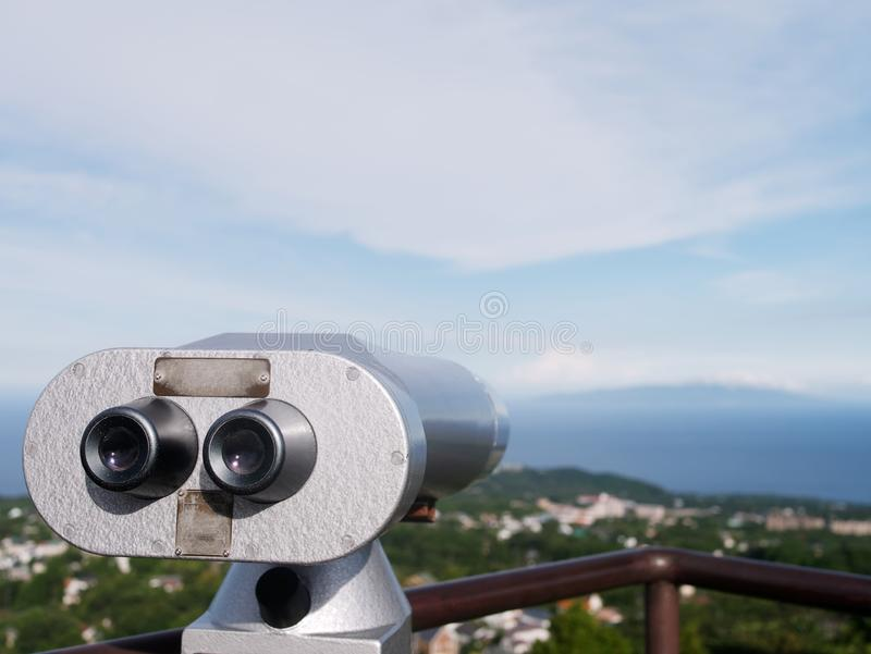 Silver coin operated binoculars looking out. Over the coastline and the sea stock images