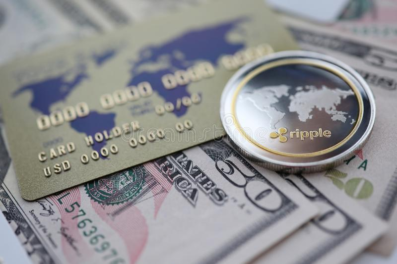 Silver coin ripple XRP closeup lie on table. With dollar paper and credit card aganist table background. Cryptocurrency exchange concept stock photography
