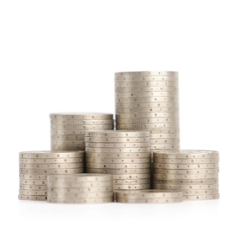 Silver coins stand vertically in low columns. Isolated on white. Symmetrically posed coins symbolise weath, richness, income and profit. Close up shot royalty free stock photography