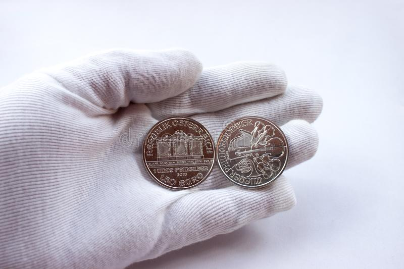 Silver coins Vienna Philharmonic Orchestra. On a white glove are silver coins of an investment silver from an Austrian mint. Vienna Philharmonic Orchestra royalty free stock images