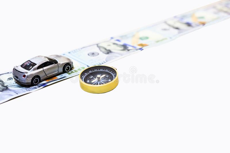 Silver color car on the money road with gold compass to guide to the right direction to wealth, isolated with clipping path royalty free stock photo