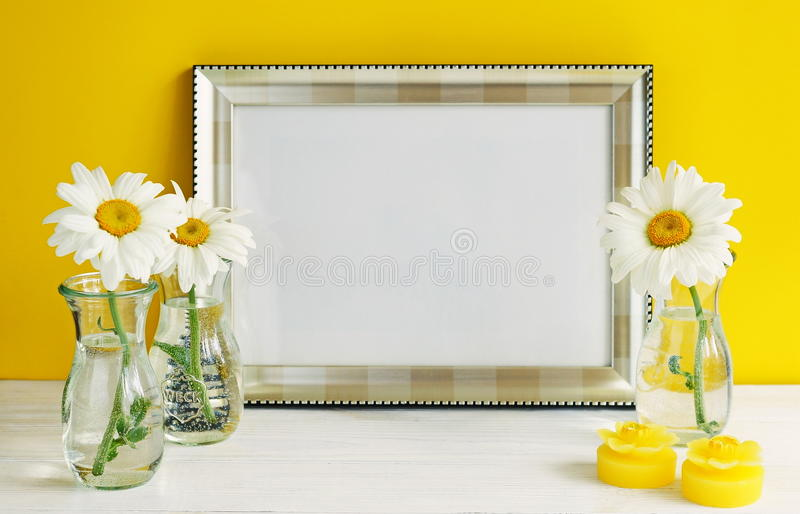 Silver color frame mockup with chamomile flowers in vases on a yellow background. Copy space stock photo