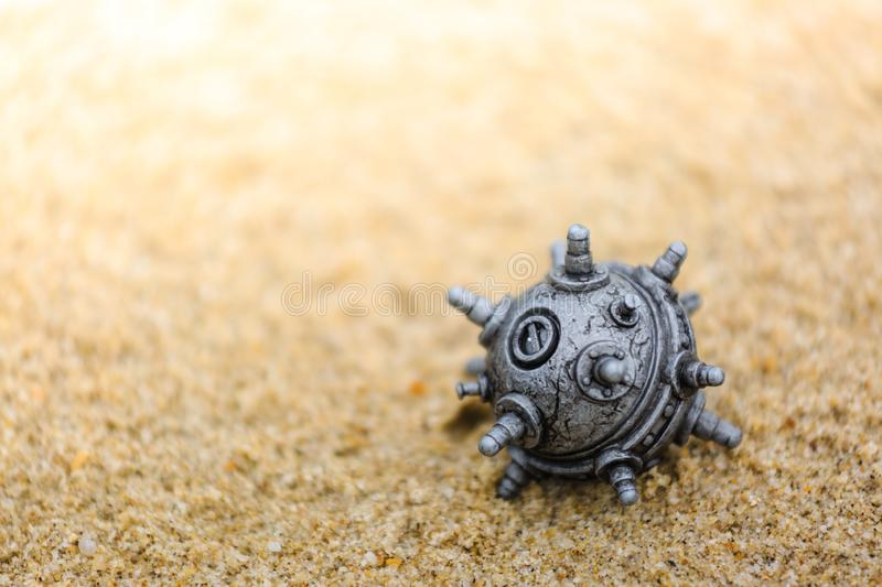 Silver color mine toy on the sands stock photography