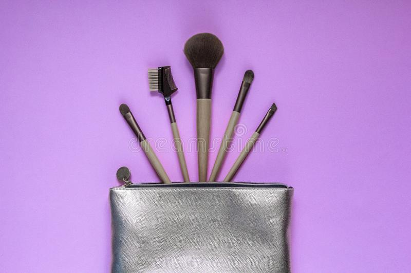 Silver cosmetic bag with makeup brushes on a pink background. Set of decorative accessories for woman. Top view, flat lay royalty free stock photography