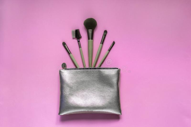 Silver cosmetic bag with makeup brushes on a pink background. Set of decorative accessories for woman. Top view, flat lay royalty free stock photo