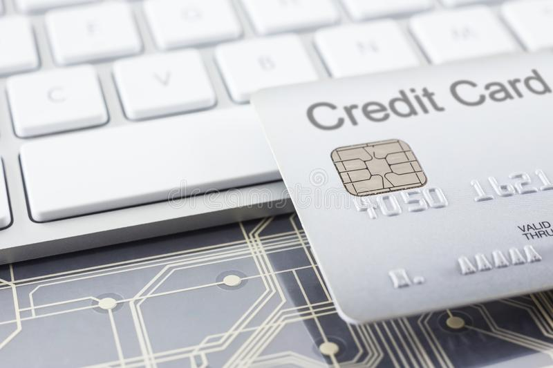 Silver credit card with digital circuits and keyboard stock photography