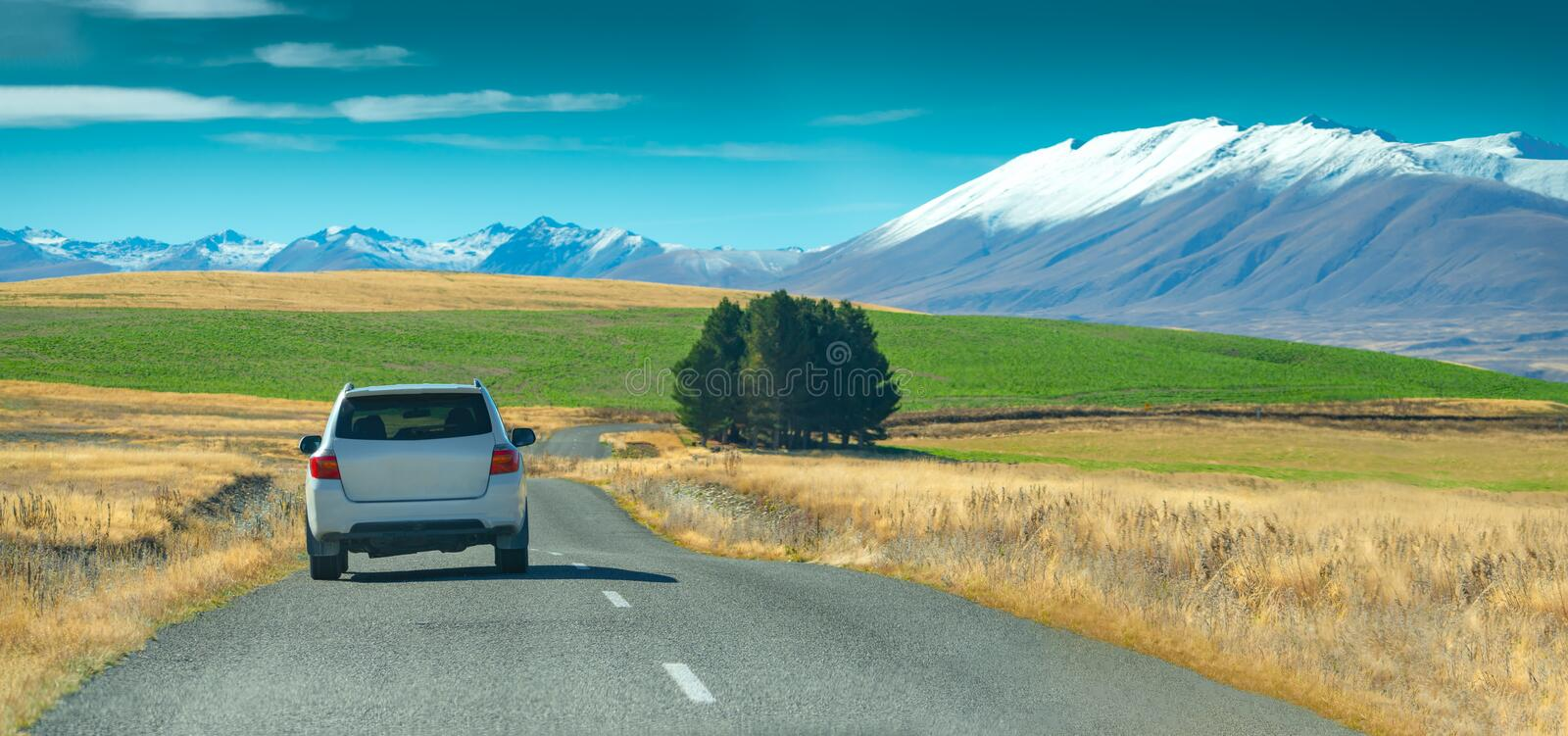 A silver crossover car driving fast on the countryside asphalt road against blue sky with white clouds. A long straight road stock image