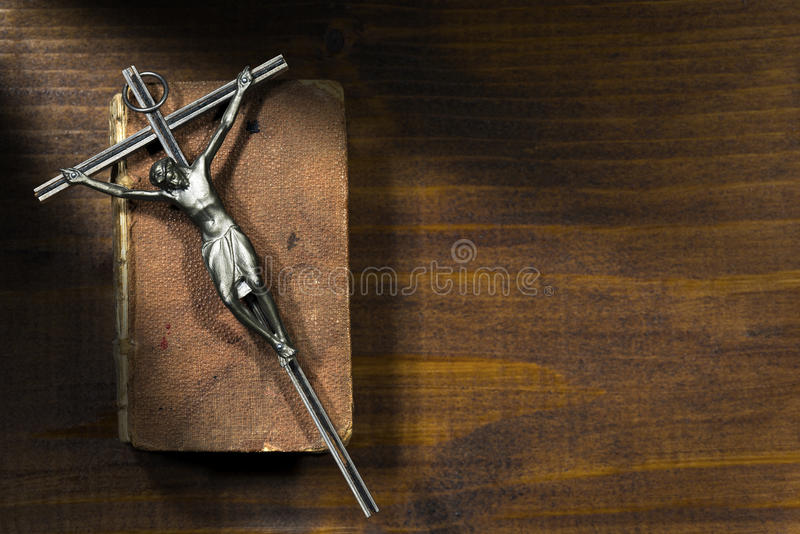 Silver Crucifix and Holy Bible on Wooden Background. Silver crucifix on an aged Holy Bible on a wooden table with dark shadows stock photography