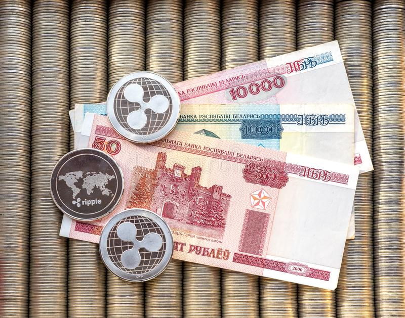 Silver crypto coins Ripple XRP, paper denominations Belarusian ruble. Metal coins are laid out in a flat background, close-up view. From top, crypto currency stock photos