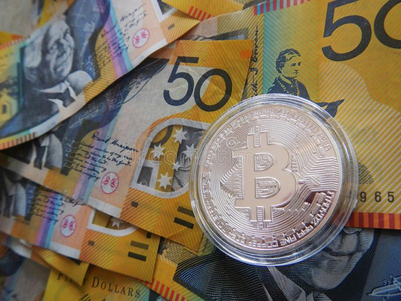 Bitcoin on Australian dollar. Silver cryptocurrency Bitcoin on Australian $50 dollar notes stock image