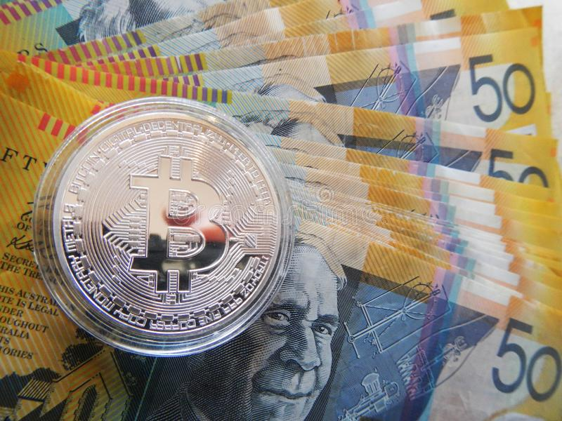 Bitcoin on Australian dollar. Silver cryptocurrency Bitcoin on Australian $50 dollar notes royalty free stock photos