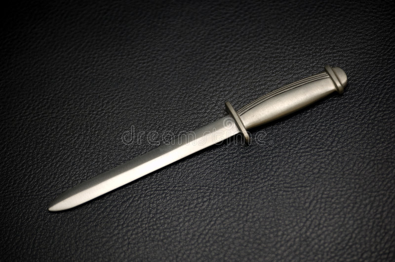 Silver Dagger on Black Leather stock images