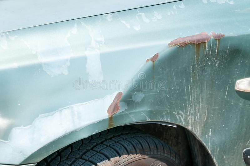 Silver damaged and broken car with dented aluminum metal body scratched and peeling paint from crash accident or collision.  stock photo