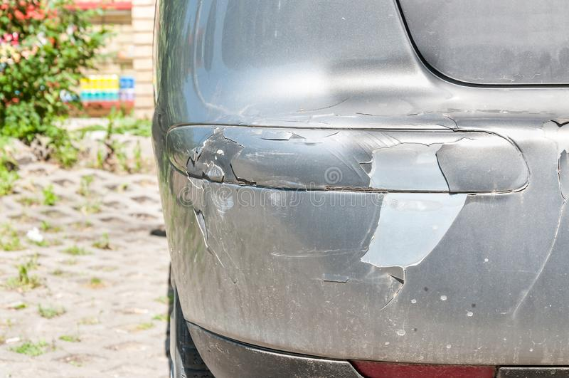 Silver damaged and broken car with dented aluminum metal body scratched and peeling paint from crash accident or collision.  royalty free stock photography