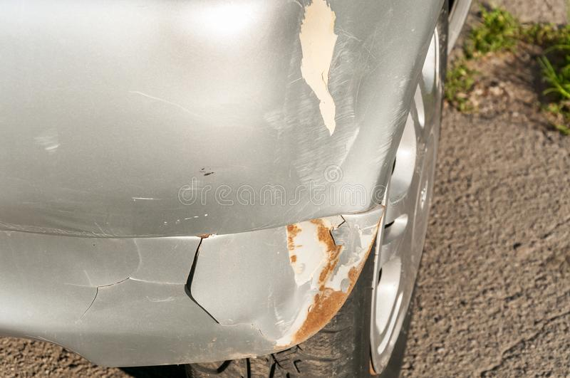 Silver damaged car in crash accident or collision with scratched paint and dented rear bumper metal body royalty free stock images