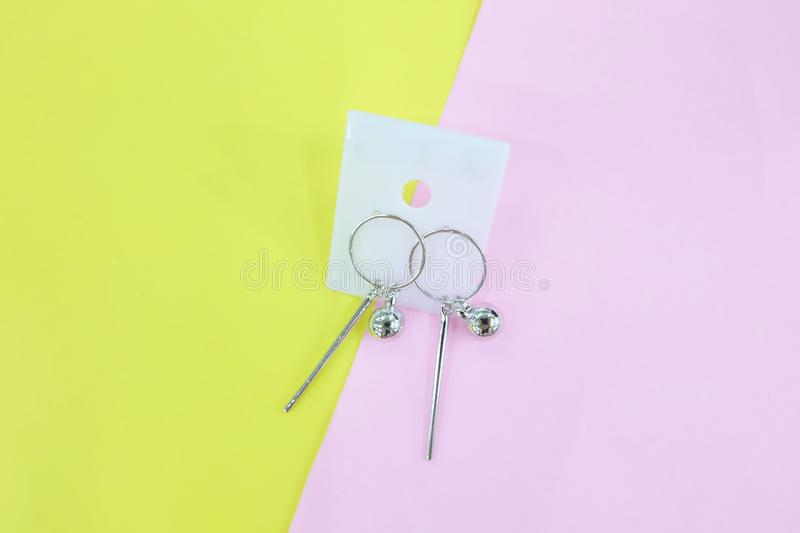 Silver Earring Accessories. Drop Round Earrings Isolated on Yellow and Pink Pastel Background. Great For Any Use stock images