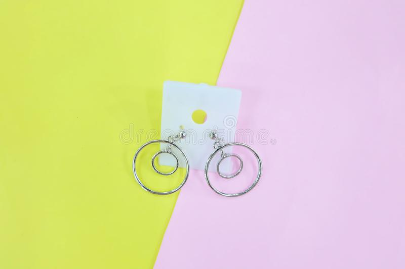 Silver Earring Accessories. Drop Round Earrings Isolated on Yellow and Pink Pastel Background. Great For Any Use royalty free stock photo