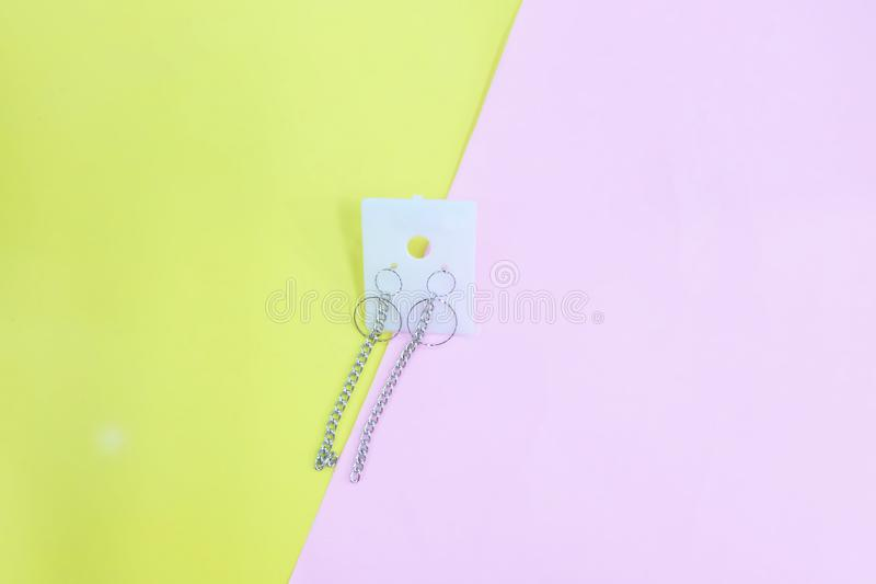 Silver Earring Accessories. Drop Round Earrings Isolated on Yellow and Pink Pastel Background. Great For Any Use stock image