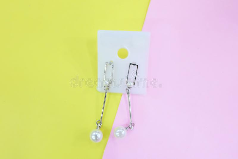 Silver Earring Accessories. Drop Round Earrings Isolated on Yellow and Pink Pastel Background. Great For Any Use stock photos