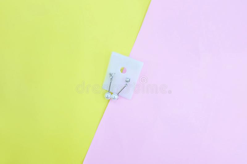 Silver Earring Accessories. Drop Round Earrings Isolated on Yellow and Pink Pastel Background. Great For Any Use stock photo