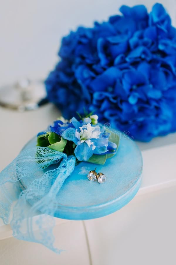 Silver earrings with gems on a wooden stand, with a blue hydrangeas on background. Wedding. Artwork royalty free stock photos