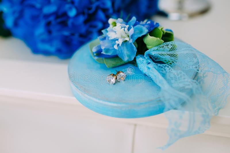 Silver earrings with gems on a wooden stand, with a blue hydrangeas on background. Wedding. Artwork stock photo
