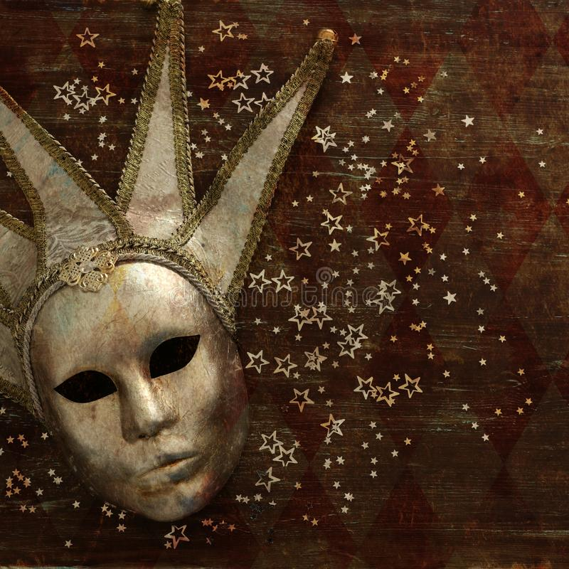 silver elegant traditional venetian mask over dark wooden background. royalty free stock photo