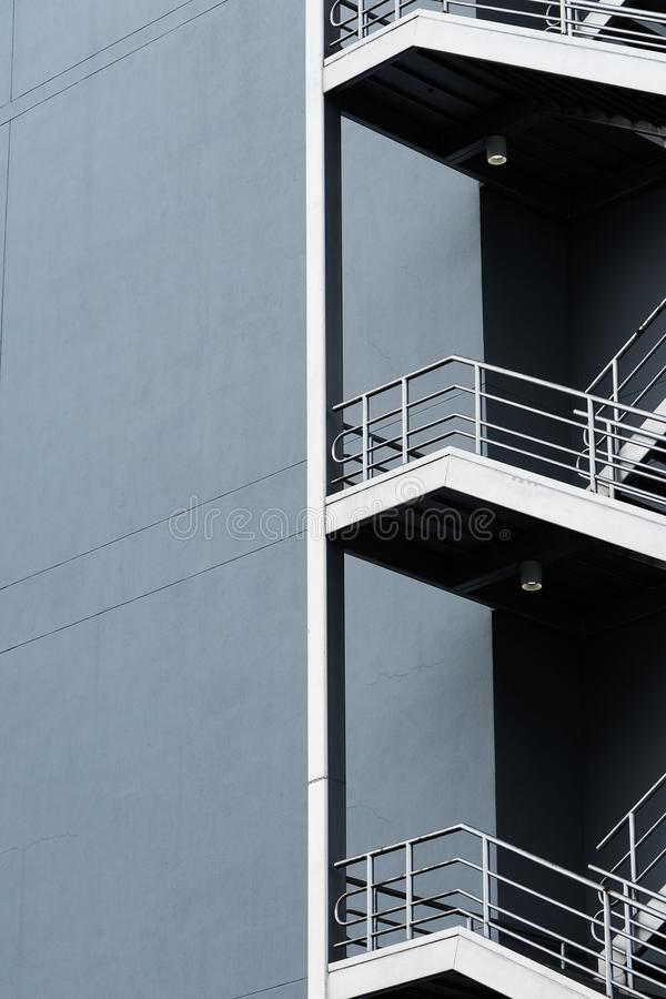 Silver emergency stairs in gray building stock images