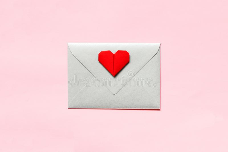 Silver envelope and origami heart on pink background. royalty free stock photo