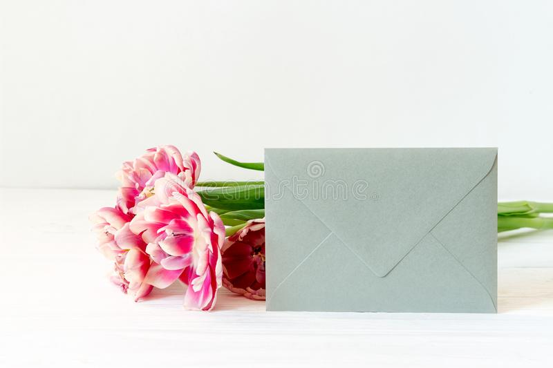 Silver envelope and pink tulips on wooden background stock photography