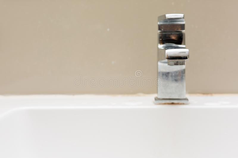 Silver faucet in bathroom,flow of water from faucet stock image