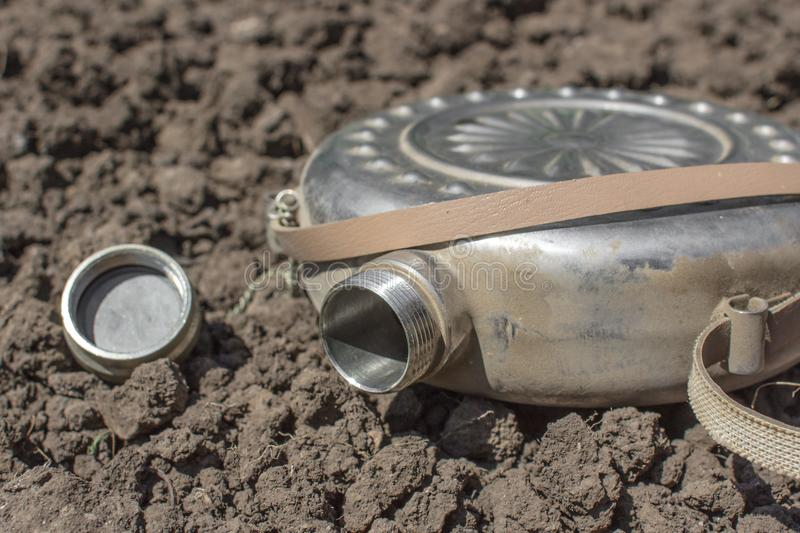 Silver flask without water on the ground royalty free stock photo
