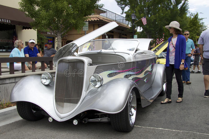 Silver 1933 Ford Roadster Street Rod at the auto show. Vintage silver convertible (Ford Roadster Street Rod 1933) with a raised hood. The picture was taken at stock image