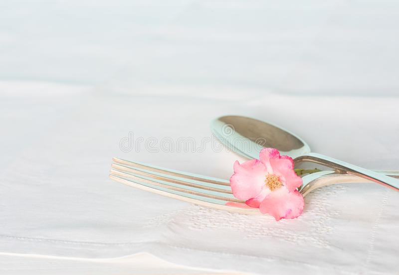 Sterling Fork and Spoon on Vintage White Table cloth with one Pink Rose. Silver Fork and Spoon with a Pink Rose on White Table Cloth with Room or Space for your royalty free stock photo