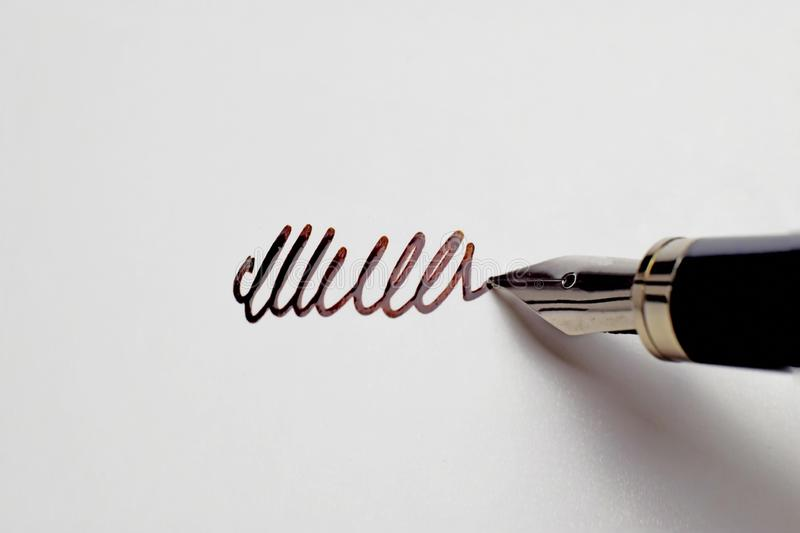 Silver fountain pen making the signature to the blank white paper with the ink royalty free stock image