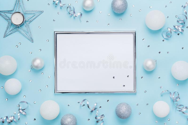 Silver frame and christmas decoration on stylish blue table top view. Fashion background. Flat lay. Party mockup, invitation. stock photo