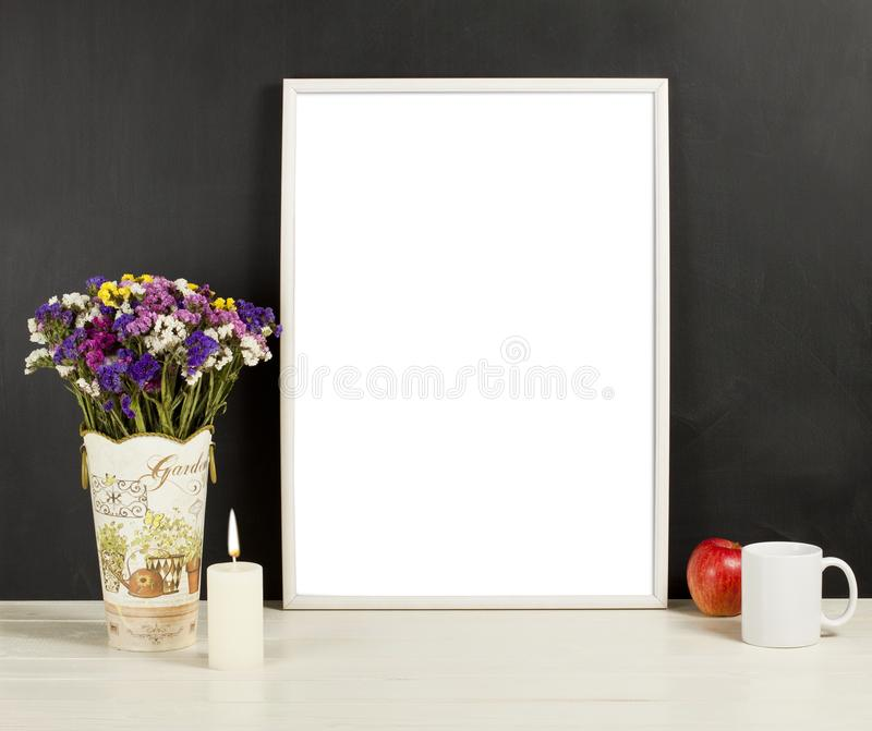 Silver frame mockup with field flowers in vase, apple, mug and c. Andle. Empty frame mock up for presentation design. Template framing for modern art royalty free stock images