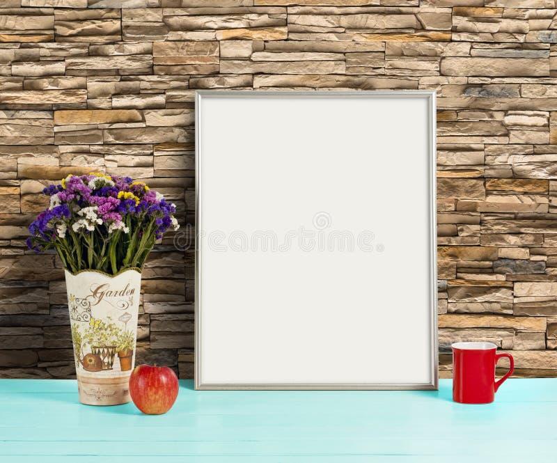 Silver frame mockup with field flowers in vase, apple and mug. Empty frame mock up for presentation design. Template framing for modern art stock image