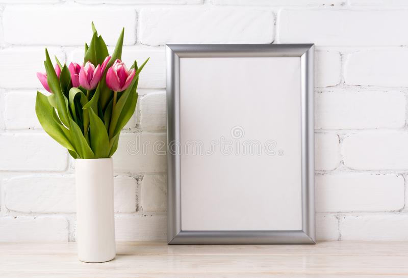 Silver frame mockup with pink tulips in vase. Silver frame mockup with bright pink tulips bouquet in vase near white painted brick wall. Empty frame mock up for royalty free stock image