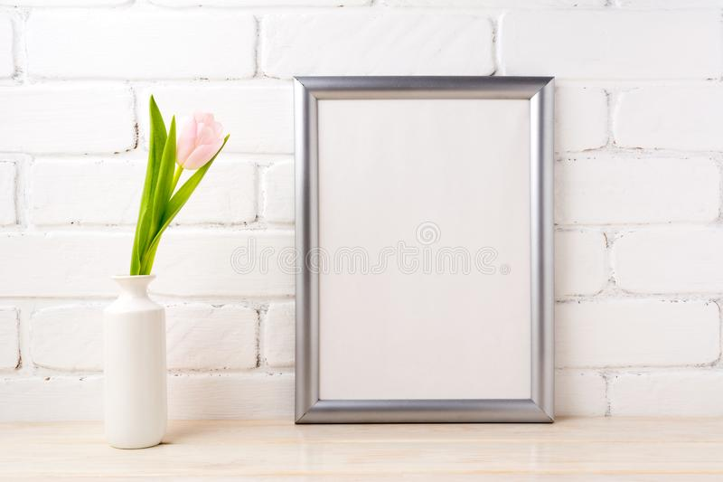 Silver frame mockup with tender soft pink tulip. Silver frame mockup with soft pink tulip in white vase near white painted brick wall. Empty frame mock up for royalty free stock photos
