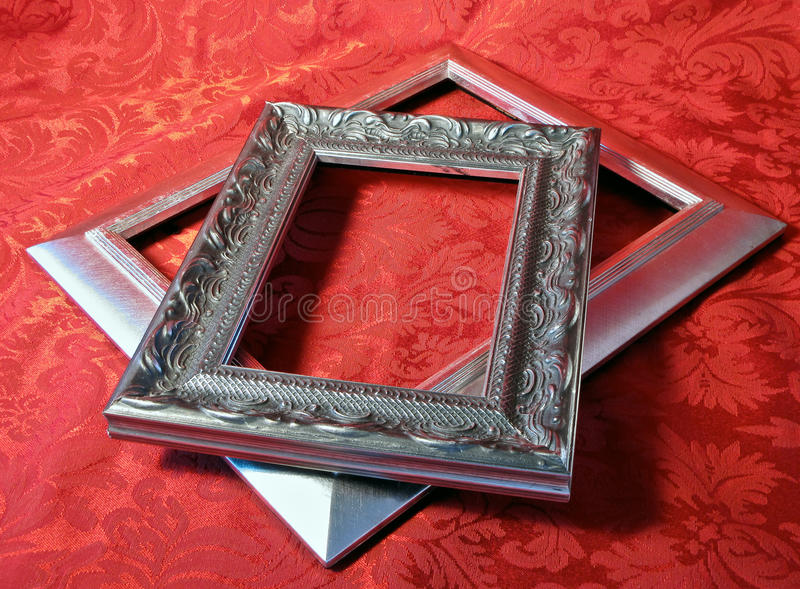 Silver frames. Silver Picture Frames stacked on a red brocade textile stock photography