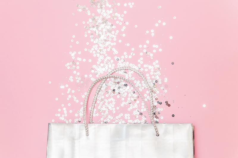 Silver gift bag with glitters confetti on a pink background flat lay. Christmas, winter, birthday, celebration, shopping, sale stock images