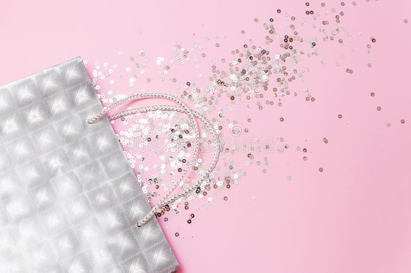 Silver gift bag with glitters on a light pink background flat lay. Christmas, winter, birthday, celebration, shopping, sale royalty free stock photos