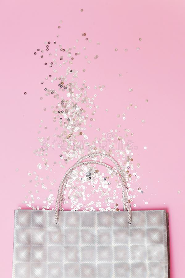 Silver gift bag with glitters on a pink background flat lay vertical. Christmas, winter, birthday, celebration, shopping, sale royalty free stock photo