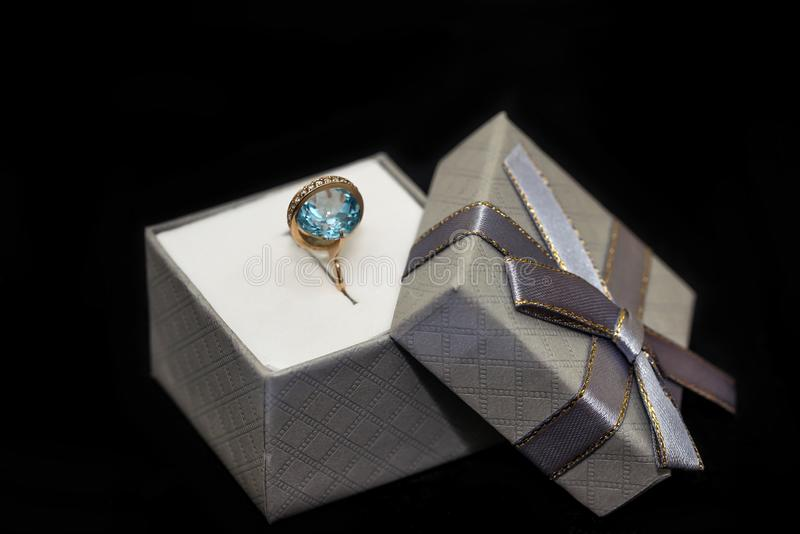 Silver gift box with ring isolated on black.  royalty free stock image