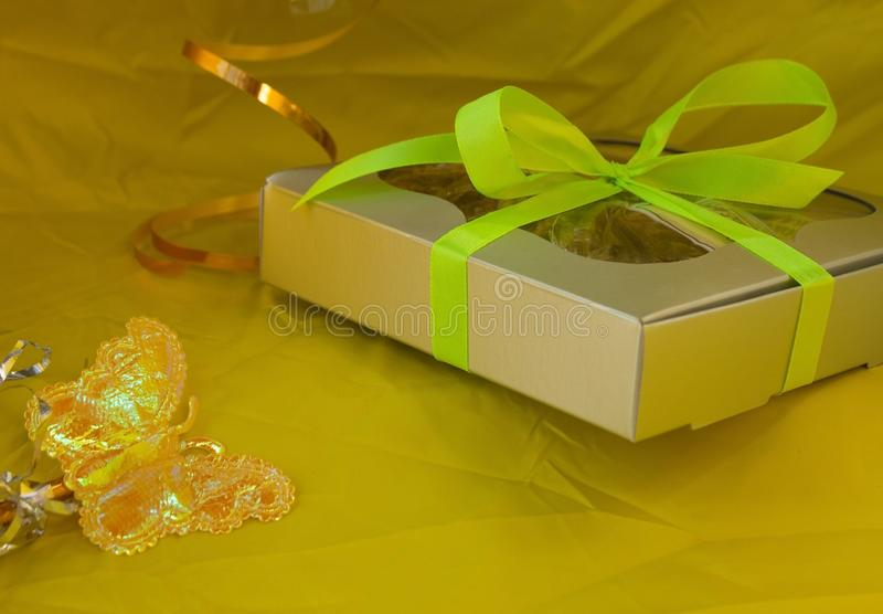Silver gift box tied yellow ribbon bow on yellow background stock photo